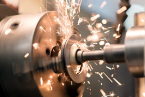 metalworking industry finishing metal working on lathe grinder machine with flying sparks