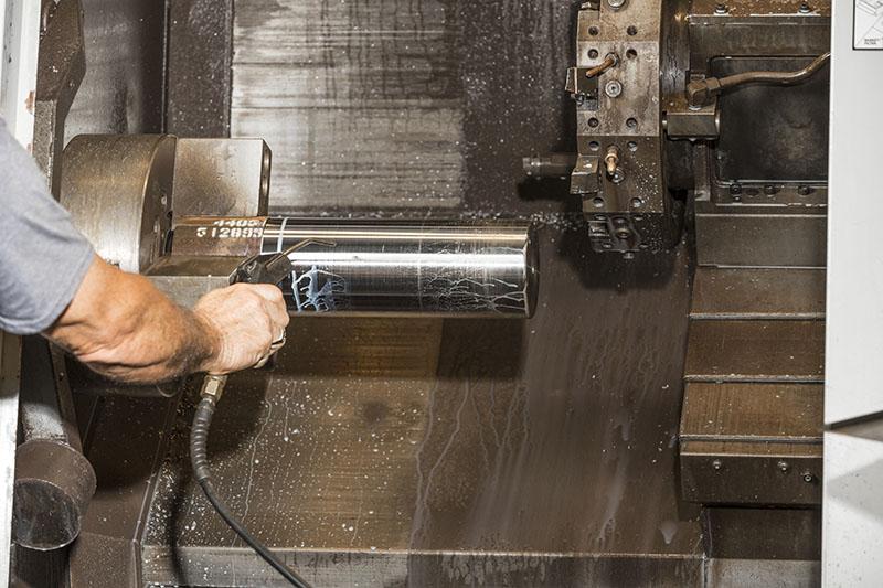 man processing a pump plunger